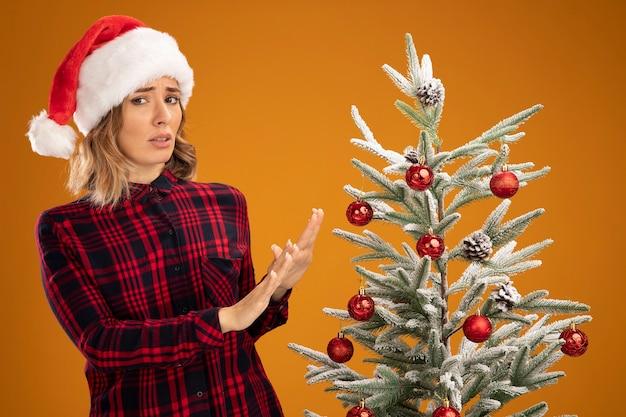 Menina linda e desagradável em pé perto de uma árvore de natal com chapéu de natal e as mãos estendidas para uma árvore isolada em fundo laranja