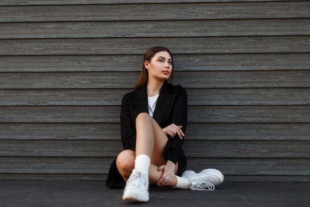 Menina linda e elegante com um casaco preto na moda e sapatos brancos, sentada perto de uma parede de madeira