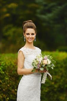 Menina linda e elegante modelo morena com maquiagem brilhante e penteado de casamento