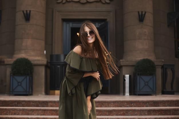 Menina linda e elegante modelo morena com um sorriso encantador, em um vestido elegante com ombros nus e os óculos de sol da moda posando ao ar livre em frente ao antigo edifício
