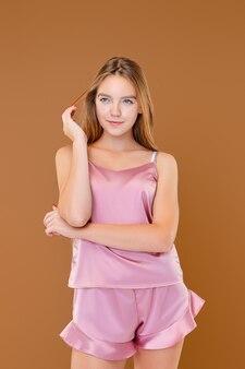 Menina linda e feliz em roupa de noite rosa com pele saudável e cabelo longo e reto