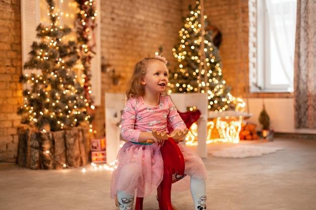 Menina linda e feliz em um vestido da moda cavalga em um balanço vermelho no fundo de uma árvore de natal, luzes e enfeites de casa