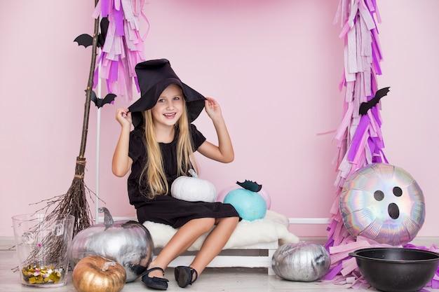 Menina linda e fofa criança com fantasia de carnaval de bruxa em decorações de halloween da moda
