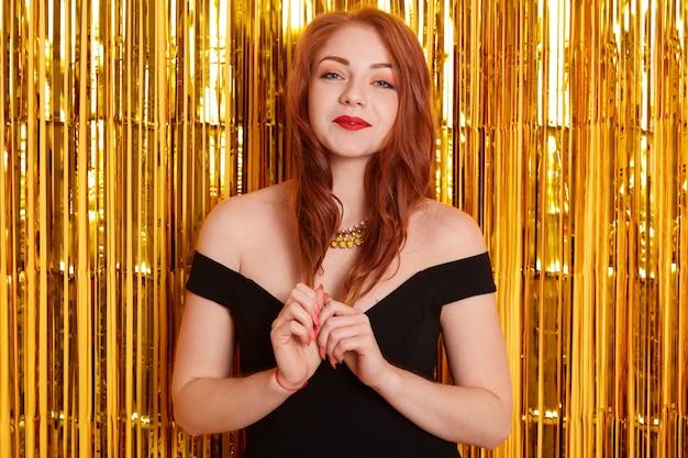 Menina linda e gentil de cabelos ruivos no espaço com enfeites dourados, olhando para a câmera, tocando seus cachos