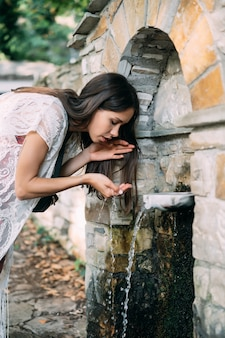 Menina linda e jovem bebe água de nascente ao ar livre