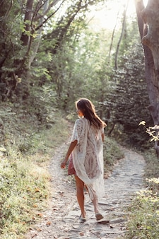 Menina linda e jovem caminha ao pé da montanha ao longo