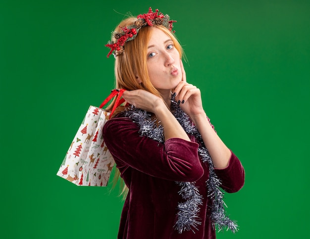 Menina linda e satisfeita com um vestido vermelho com grinalda e guirlanda no pescoço, segurando uma sacola de presente no ombro, isolada no fundo verde