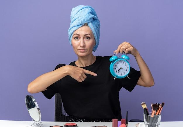 Menina linda e satisfeita se senta à mesa com ferramentas de maquiagem, enxugando o cabelo na toalha, segurando e aponta para o despertador isolado na parede azul