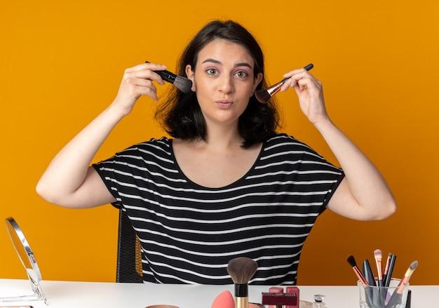 Menina linda e satisfeita sentada à mesa com ferramentas de maquiagem segurando pincéis de pó ao redor do rosto isolado na parede laranja