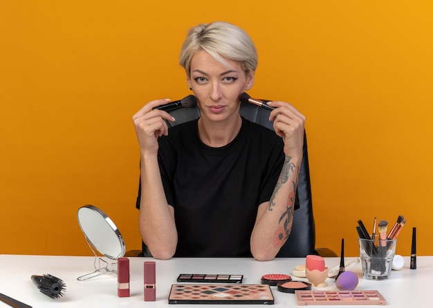 Menina linda e satisfeita sentada à mesa com ferramentas de maquiagem segurando pincéis de pó no rosto isolado na parede laranja