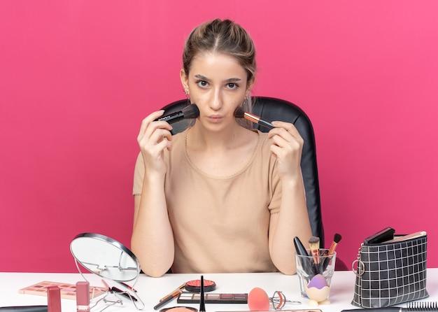 Menina linda e satisfeita sentada à mesa com ferramentas de maquiagem segurando um pincel para pó isolado na parede rosa