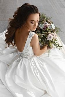 Menina linda e sexy modelo morena em um vestido de noiva elegante com um grande buquê de luxo de f ...