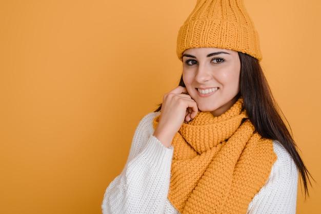 Menina linda e sorridente em um chapéu de malha e com um lenço posa lindamente no estúdio