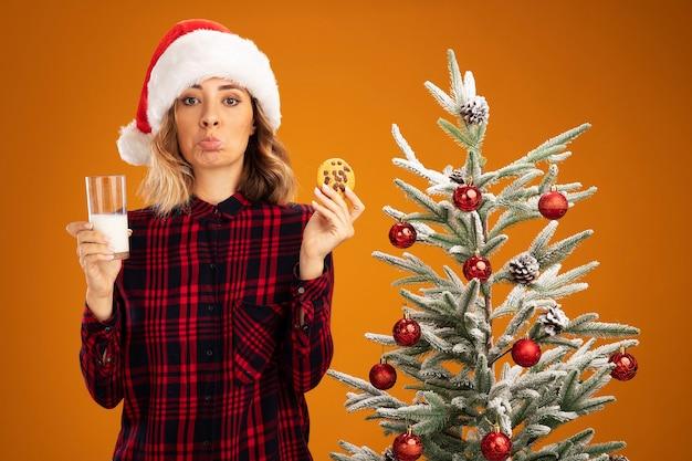 Menina linda e triste em pé perto da árvore de natal, usando um chapéu de natal, segurando um copo de leite com biscoitos isolados em um fundo laranja