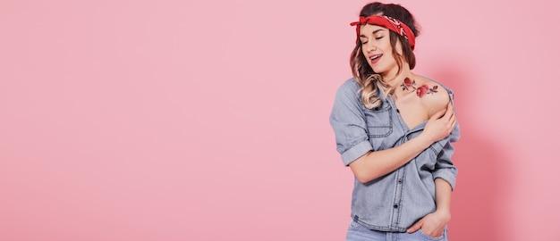 Menina linda em camisa jeans com etiqueta de flores de tatuagem de água decalque e sorrindo em fundo rosa