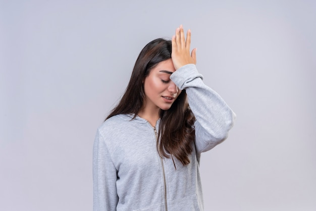 Menina linda em um capuz cinza tocando a cabeça por engano, parecendo um conceito de memória ruim confuso em pé sobre um fundo branco
