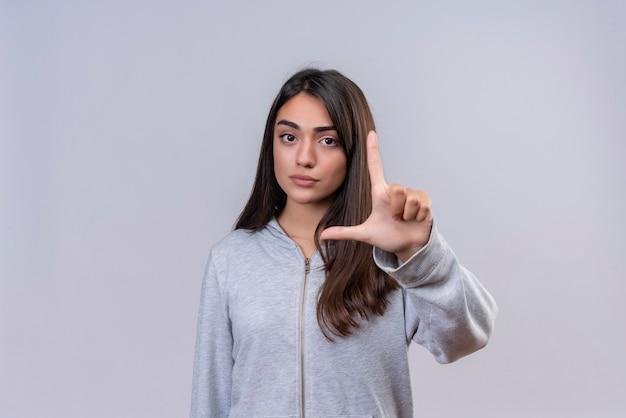 Menina linda em um casaco cinza com capuz mostrando uma placa de tamanho pequeno com o símbolo de medida de rosto sério em pé sobre um fundo branco