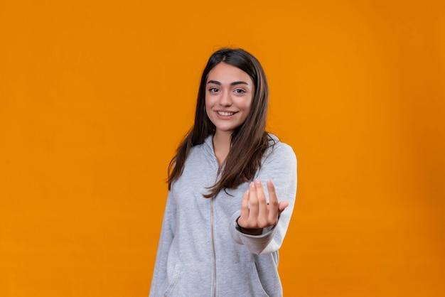 Menina linda em um casaco cinza com capuz olhando para a câmera com um sorriso e estendendo a mão em pé sobre um fundo laranja