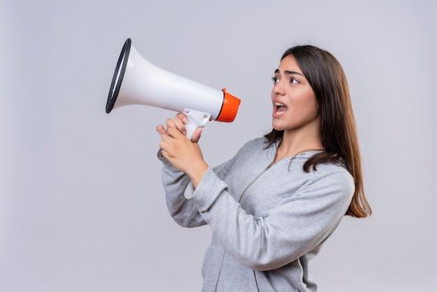 Menina linda em um casaco cinza com capuz olhando para longe e gritando para o alto-falante em pé sobre um fundo branco