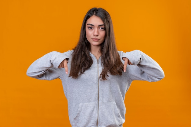 Menina linda em um casaco com capuz cinza apontando para baixo e descontente em pé sobre um fundo laranja
