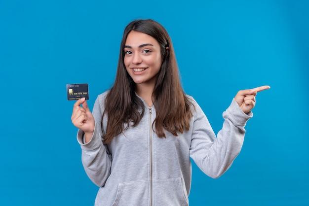 Menina linda em um casaco com capuz cinza olhando para a câmera com um sorriso no rosto, segurando o cartão de crédito e apontando a outra mão em pé sobre um fundo azul