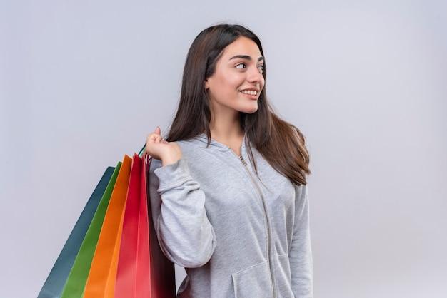 Menina linda em um casaco com capuz cinza olhando para longe com um sorriso no rosto segurando pacotes sobre um fundo branco