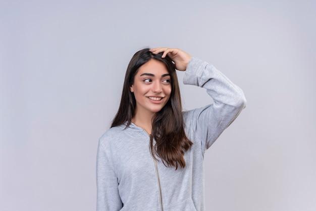 Menina linda em um casaco com capuz cinza olhando para longe e o sorriso da câmera no rosto tocando a cabeça em pé sobre um fundo branco