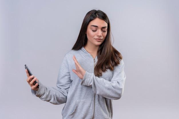 Menina linda em um casaco com capuz cinza segurando o telefone, sem olhar para o telefone em pé sobre um fundo branco