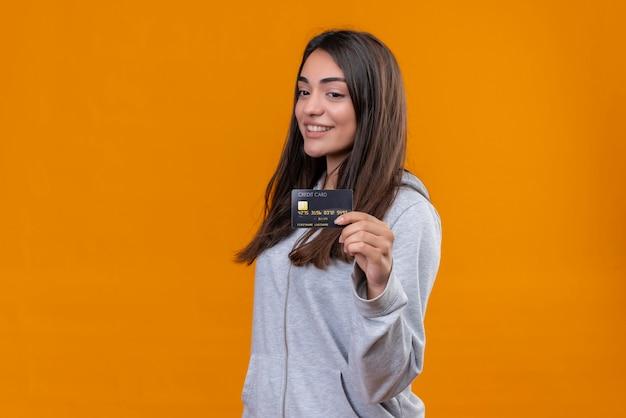 Menina linda em um casaco com capuz cinza segurando um cartão de crédito e olhando para o cartão de crédito com um sorriso no rosto em pé sobre um fundo laranja