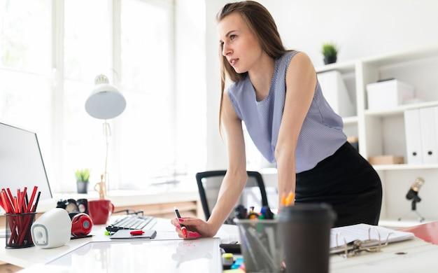 Menina linda em um escritório está de pé perto de uma mesa e desenha um marcador em um quadro magnético.