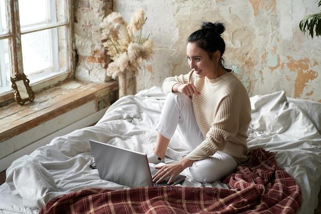 Menina linda em um suéter aconchegante na cama em casa, trabalhando em um laptop