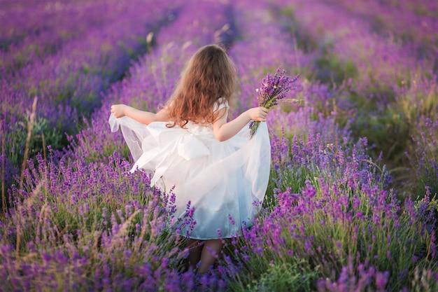 Menina linda em um vestido branco andando com um buquê em um campo de lavanda