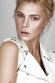 Menina linda em um vestido branco com uma maquiagem natural leve