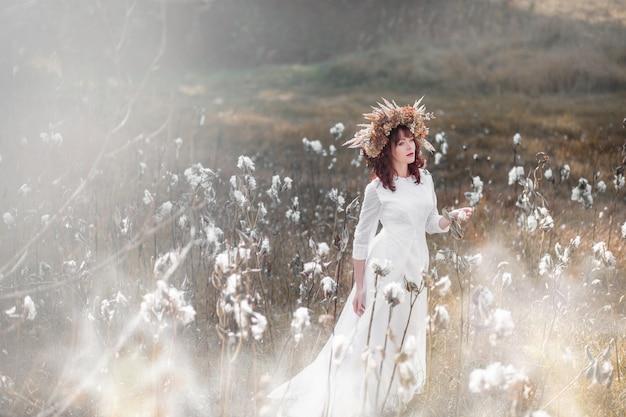 Menina linda em um vestido branco vintage e grinalda de flores secas na cabeça em um campo de outono