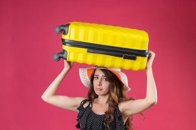 Menina linda em um vestido de bolinhas com chapéu de verão segurando a mala na mão, parecendo cansada e entediada em pé sobre um fundo rosa