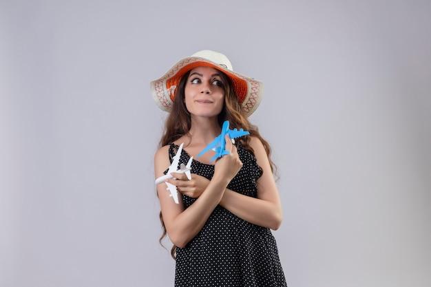 Menina linda em um vestido de bolinhas com chapéu de verão segurando aviões de brinquedo, parecendo alegre, feliz e positiva em pé sobre um fundo branco