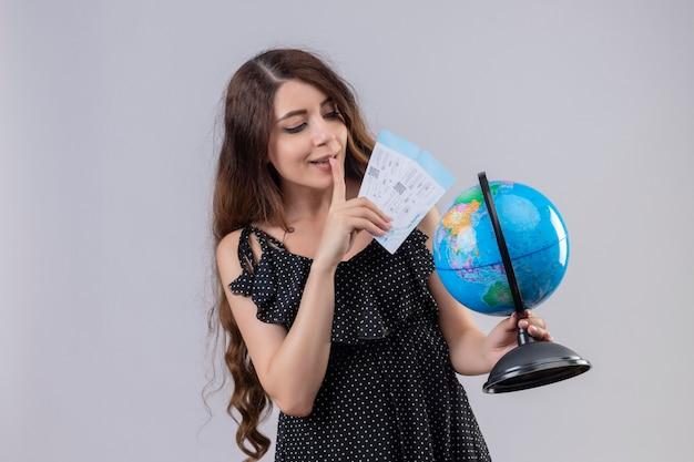 Menina linda em um vestido de bolinhas segurando passagens aéreas e um globo olhando para ele intrigada e feliz em pé sobre um fundo branco