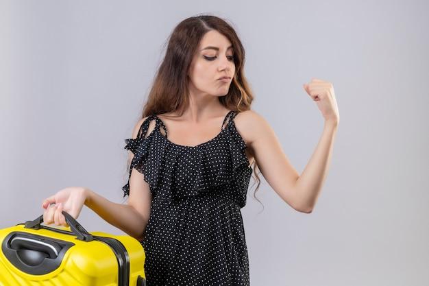Menina linda em um vestido de bolinhas segurando uma mala de viagem levantando o punho e mostrando o bíceps parecendo confiante e satisfeito em pé sobre um fundo branco