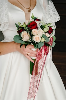 Menina linda em um vestido elegante está de pé e segurando o buquê de flores pastel e verdes com fita na natureza.