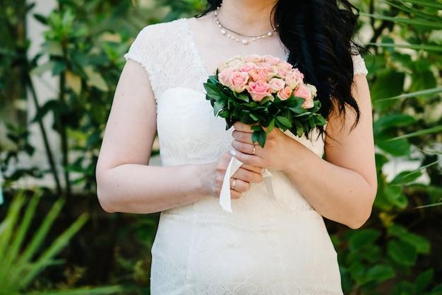 Menina linda em um vestido elegante está de pé segurando um buquê de flores rosa pastel