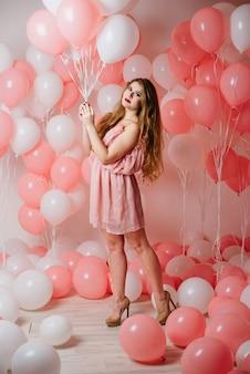 Menina linda em um vestido entre muitas bolas cor de rosa.