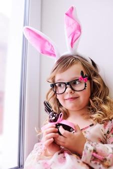 Menina linda em um vestido inteligente com orelhas de coelho na cabeça, segurando um coelhinho da páscoa de chocolate