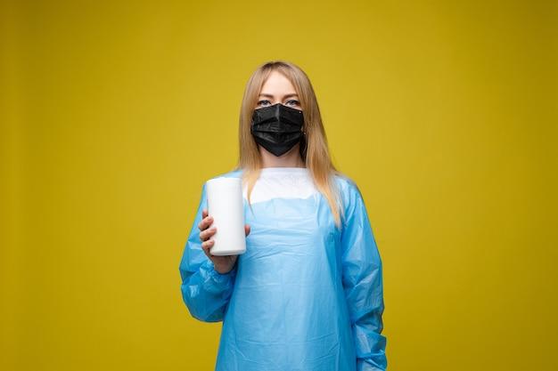 Menina linda em um vestido médico descartável e com uma máscara no rosto segurando lenços umedecidos antibacterianos, retrato isolado em fundo amarelo
