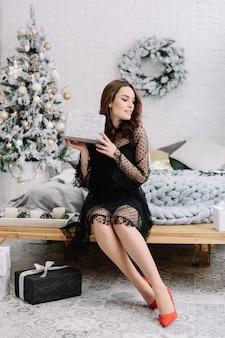 Menina linda em um vestido preto com presentes nas mãos