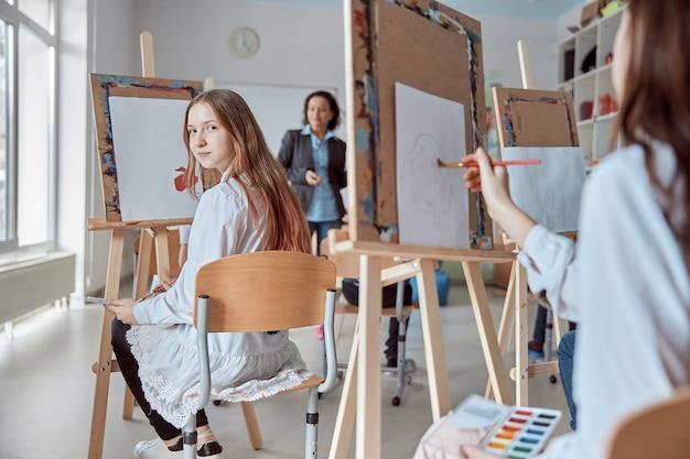 Menina linda em uma aula de desenho em grupo