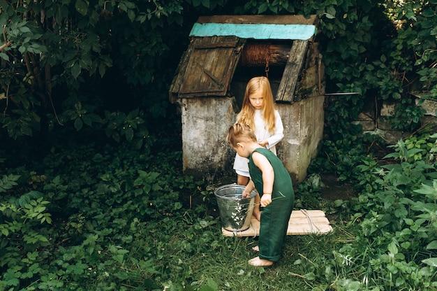 Menina linda em uma camisa branca com um menino em uma combinação verde perto do poço