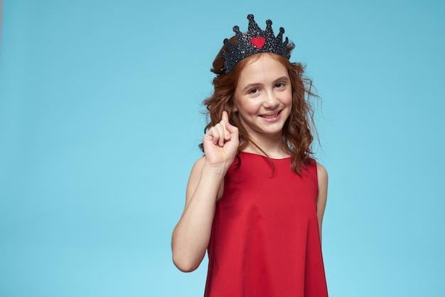 Menina linda em uma coroa, princesa, bebê fofo no estúdio em uma parede azul