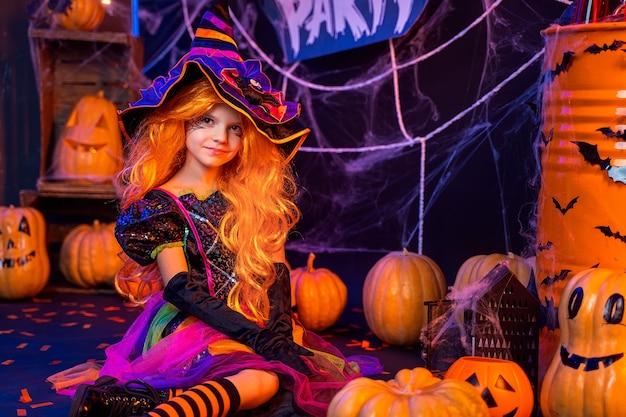 Menina linda em uma fantasia de bruxa celebra a festa de feliz dia das bruxas no interior com abóboras.
