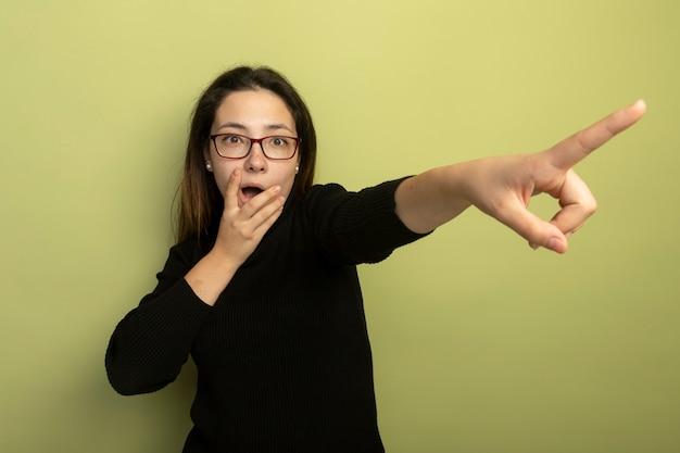 Menina linda em uma gola alta preta e óculos apontando com o indicador figner para algo ficando surpresa e preocupada