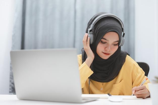 Menina linda estudante muçulmana usando um computador portátil, aprendendo on-line em casa. educação online a distância.
